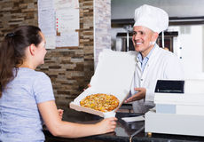 Mature man chef serving fresh pizza to customer Royalty Free Stock Photo