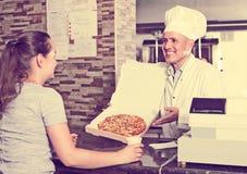 Mature man chef serving fresh pizza to customer Stock Photo