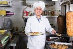 Mature man chef wearing uniform cooking kebab Stock Images
