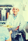 Mature man chef wearing uniform giving kebab plate to customer Stock Images