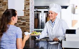 Mature man chef wearing uniform giving kebab plate to customer Stock Photography