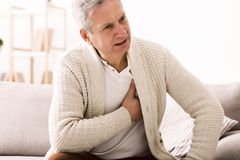 Mature man with chest pain, suffering from heart attack. At home stock photos