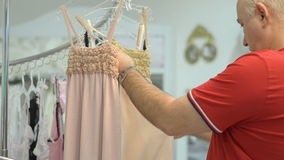 Mature man chooses for female new clothes at the mall. Royalty Free Stock Images