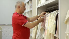 Mature man chooses for female new clothes at the mall. Royalty Free Stock Photo