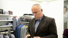 Mature man chooses for himself new clothes Royalty Free Stock Image