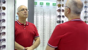 Mature man chooses for himself new glasses at the mall. Royalty Free Stock Photos