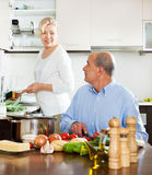 Mature man chopping vegetable and looking at his wife Royalty Free Stock Photo