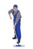 Mature man cleaning floor with mop Royalty Free Stock Images