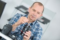 Mature man cleaning lens digital camera with special brush Royalty Free Stock Photos