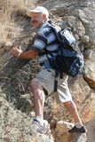 Mature man climbing on rock royalty free stock image