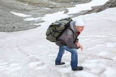 Mature man climbing on slippery steep slope of mountain on snow field Royalty Free Stock Image