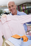 Mature man in clothing store, holding up shirt, smiling, portrait Stock Images