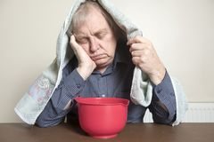 Mature man with a cold inhaling steam Royalty Free Stock Image