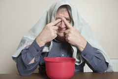 Mature man with a cold and sinus issues  inhaling steam Royalty Free Stock Photography