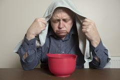 Mature man with a cold and sinus issues  inhaling steam Stock Images