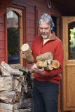Mature Man Collecting Logs For Fire From Woodpile In Garden Royalty Free Stock Photo