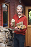 Mature Man Collecting Logs For Fire From Woodpile In Garden Stock Image