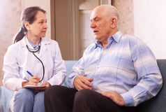 Mature man complaining to doctor about feels Stock Photography