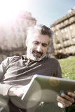 Mature man connceted on wifi in public park stock photography