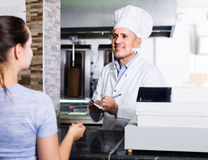Mature man cook taking order from customer on counter in fast fo Royalty Free Stock Images