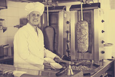 Mature man cook wearing uniform preparing kebab Royalty Free Stock Photography