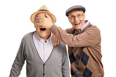 Mature man covering the eyes of his friend Stock Image