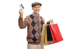 Mature man with a credit card and shopping bags. Isolated on white background Royalty Free Stock Photography
