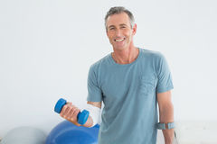 Mature man with crutch and dumbbells at gym hospital. Portrait of a smiling mature man with crutch and dumbbells at the gym hospital royalty free stock photography