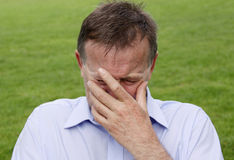 Mature man crying with hand partially covering his face. Horizontal composition Royalty Free Stock Photos