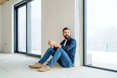 A mature man with cup of coffee sitting on the floor, furnishing new house. A new home concept. Copy space royalty free stock photo