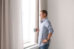 Mature man with cup of drink near window with open curtains at home. Space for text stock image