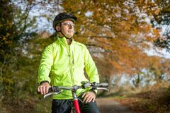 Free Mature Man Cycling Along Autumn Country Road Royalty Free Stock Photography - 191914887