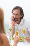Mature man dating. Dating concept be the sea. Man with black hair looking suprisingly toher woman, they both drinking delicious white wine Royalty Free Stock Image