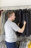 Mature man deciding what clothing to wear. Vertical portrait of mature man in walk-in closet inspecting his sweater for daily wear Royalty Free Stock Photography