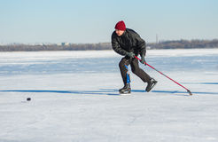 Mature man desperately trying to catch up the pack while playing hockey on a frozen river Dnepr in Ukraine Royalty Free Stock Photography