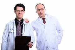 Mature man doctor with hand on shoulder of young man doctor hold. Mature men doctor with hand on shoulder of young men doctor holding clipboard stock photo