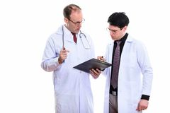 Mature man doctor and young man doctor both writing on clipboard. Mature men doctor and young men doctor both writing on clipboard isolated against white royalty free stock photos