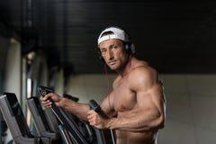 Mature Man Doing Aerobics Elliptical Walker In Gym Royalty Free Stock Images