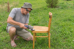 Mature man doing restoration of old chair Stock Photography