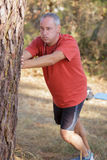 Mature man doing streches in park Stock Image