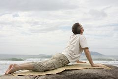Mature man doing yoga at the sea Stock Photos
