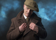 Mature man dressed as an English 1920s gangster. On a blue smoky background Stock Photo