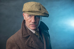 Mature man dressed as an English 1920s gangster. On a blue smoky background royalty free stock photography