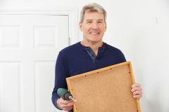 Mature Man Drilling Wall To Hang Picture Frame Stock Photography