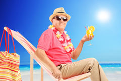 Mature man drinking cocktail on sun lounger Royalty Free Stock Photos