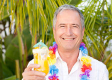 Mature man drinking a cocktail under the sun Royalty Free Stock Image
