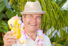 Mature man drinking a cocktail under the sun Royalty Free Stock Images