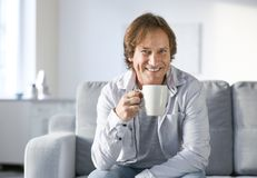 Mature man drinking coffee while sitting on sofa stock photography