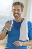 Mature Man Drinking Water From Bottle After Exercising Stock Photography