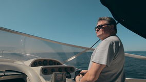 Mature man drives the yacht. And looks at the sea stock video